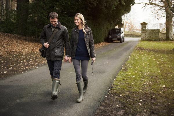 En man och en kvinna går på en väg iklädda Barbour-jackor