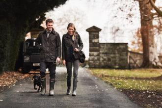 Två personer i Barbourjackor går med sin hund på en väg